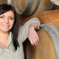 Woman standing next to barrels of wine